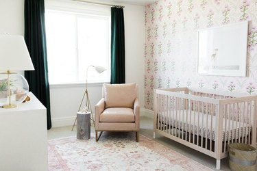 Nursery with floral wallpaper, dark green curtains, rose colored chair, floral rug.