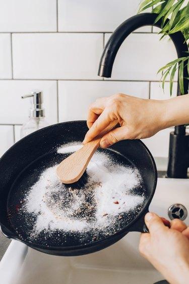 Scrub skillet with baking soda and stiff brush