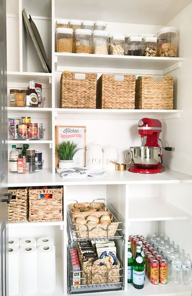Pantry with shelves, baskets, mixer, supplies.