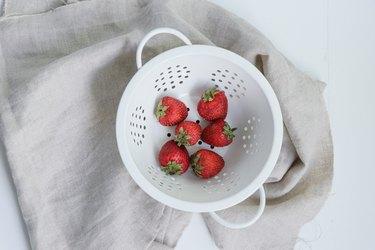 strawberries in white colander
