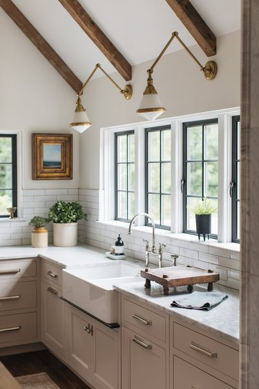 farmhouse kitchen with brass and white articulated wall sconces