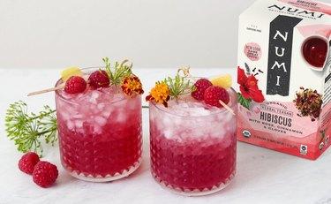 two glasses of iced hibiscus tea next to box of tea