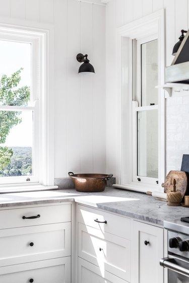 white farmhouse kitchen with black wall sconces