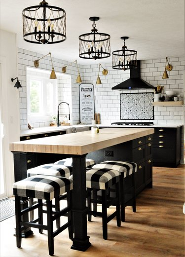 farmhouse kitchen with subway tile backsplash and three black chandeliers