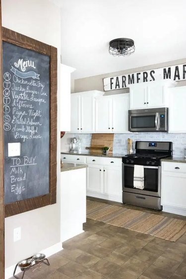farmhouse kitchen with white cabinets and black cage style ceiling light