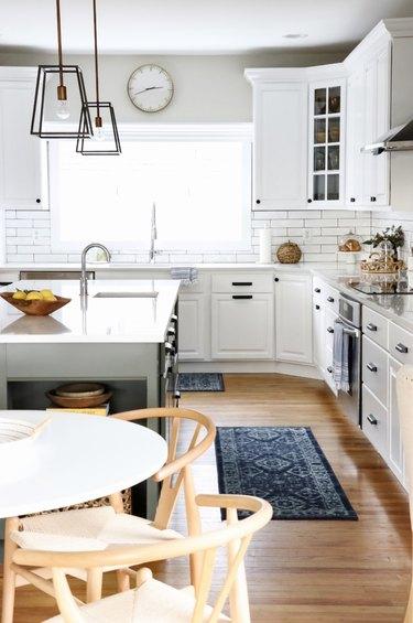 white farmhouse kitchen with sleek modern pendant lights above island