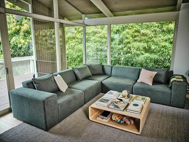 living room with green sectional couch and wood coffee table