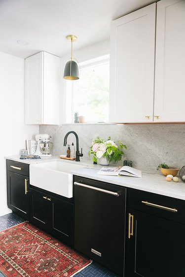 brass and black farmhouse kitchen with vintage rug