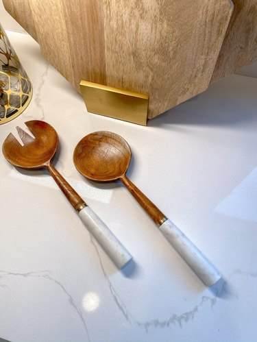 two wood serving spoons with marble handles
