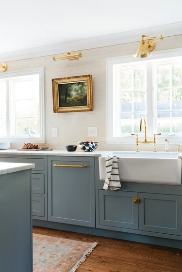 white and blue farmhouse kitchen with oil painting and picture light