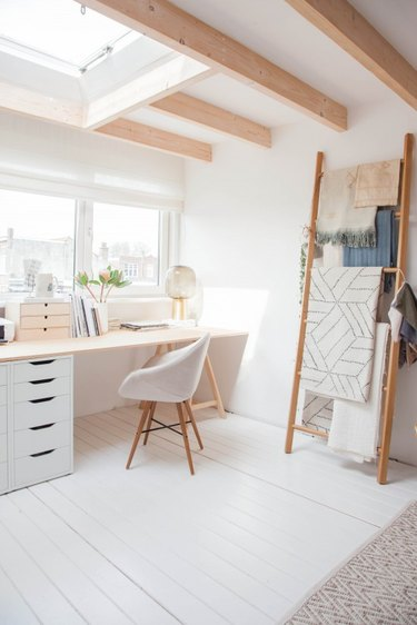 neutral home office with modern desk and blanket ladder