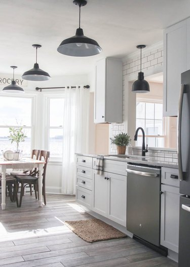 farmhouse kitchen and dining area with black pendant lights
