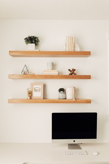 neutral home office with desktop computer and floating shelves