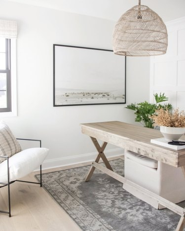 neutral home office with woven pendant light and wood desk