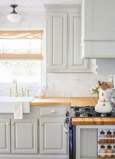 white and light green farmhouse kitchen with milk glass ceiling light