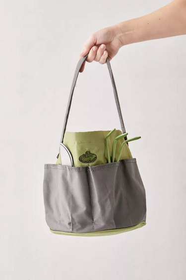 hand holding a garden tool bucket tote bag