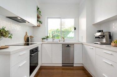 small white u-shaped kitchen with window