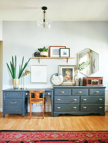 eclectic home office with blue desk that extends to a matching dresser, with a red rug and art surrounding the desk