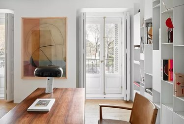 white modern minimalist home office with wooden furniture and large colorful poster on the wall
