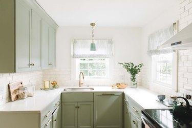 green u-shaped kitchen with white tile backsplash