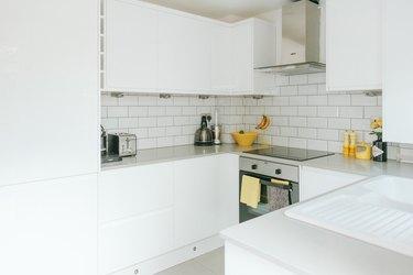 white minimalist u-shaped kitchen with yellow touches