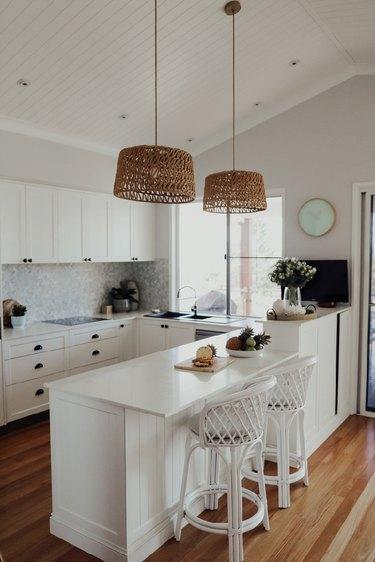 white u-shaped kitchen with rattan pendant lights