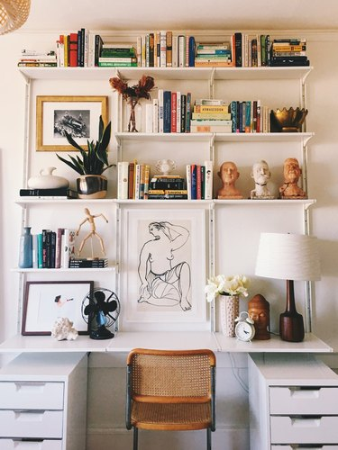 white modern home office with built-in shelving system around the desk, styled with books, sculptures and art