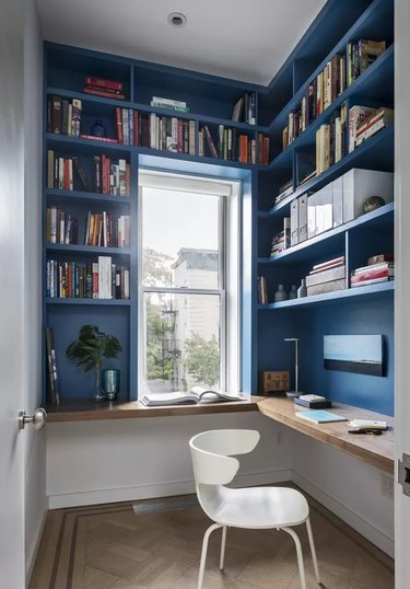 small blue home office nook with blue built-in shelving, white office chair