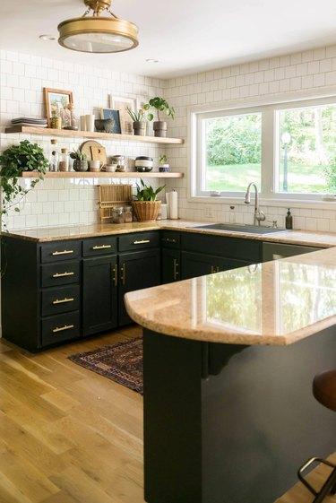 black and wood u-shaped kitchen with white tile backsplash