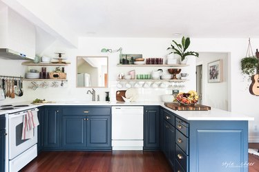 blue and white u-shaped kitchen with floating shelves