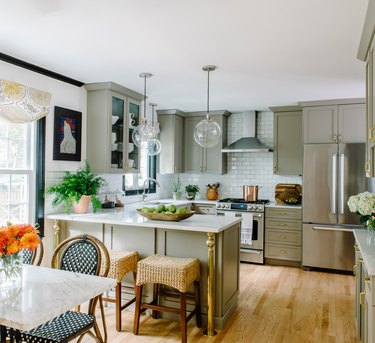green u-shaped kitchen with clear glass pendants