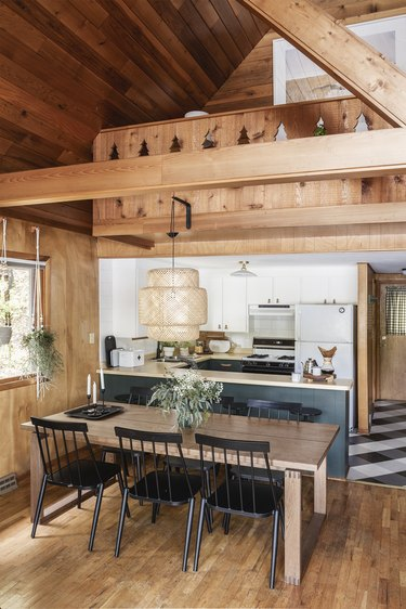 modern u-shaped kitchen next to dining area in cabin