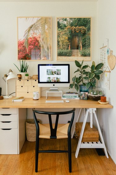 boho home office with two large photograph prints hanging above the desk, plants