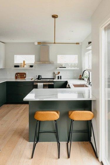 green u-shaped kitchen with modern chandelier