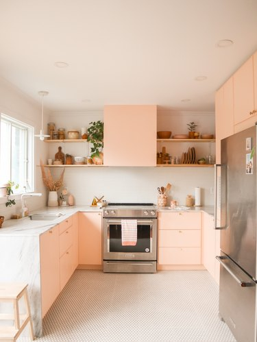pink u-shaped kitchen with wood shelves