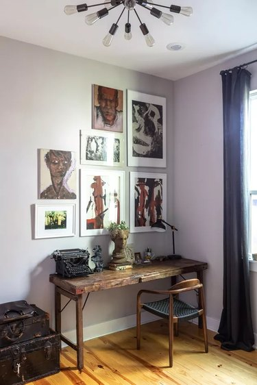 eclectic home office with gallery wall hanging above the vintage wooden desk