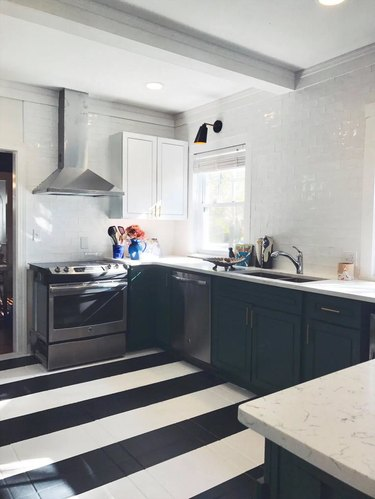 black u-shaped kitchen with black and white striped floor