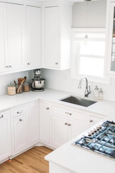 white kitchen with stainless steel sink and window