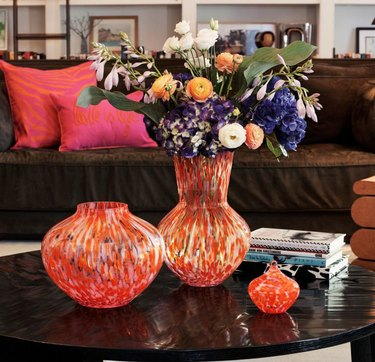 colorful vase with flowers on black coffee table with couch with pink pillows in the background