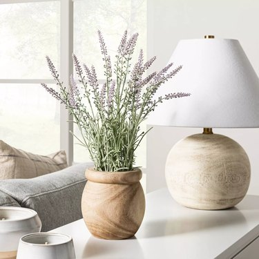 faux lavender in pot on table next to lamp