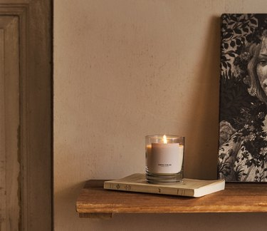 zara home candle on book next to painting of woman
