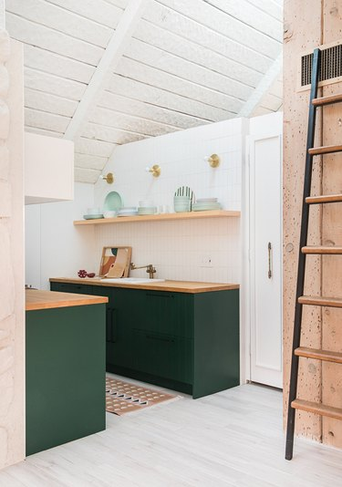 kitchenette with light wood counters, white walls and green cabinets
