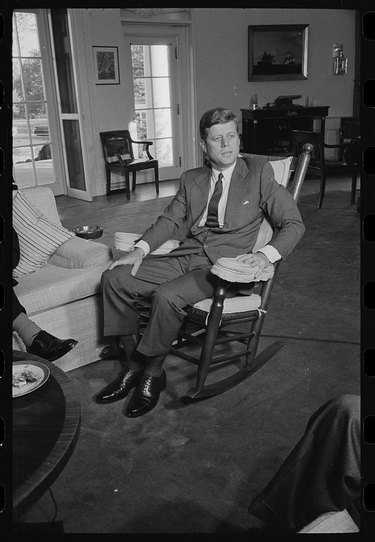 presdeint john f kennedy in a rocking chair in the white house