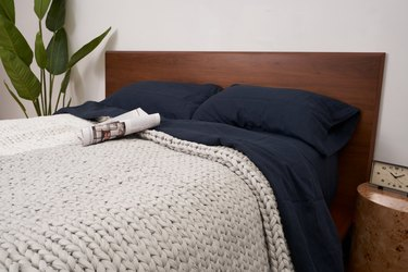 bearaby the hugger blanket on bed with navy bedding