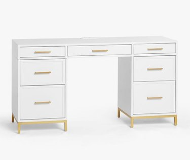 white lacquered desk with gold hardware and drawers for storage