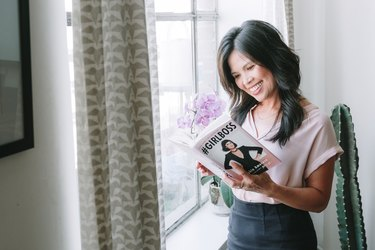 Anna Marie Cruz holding a book by a window