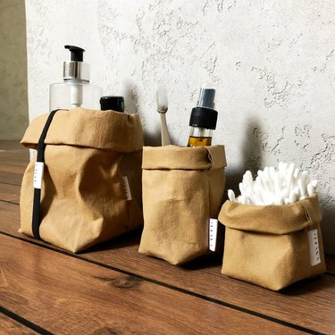 three reusable paper bags with bathroom necessities