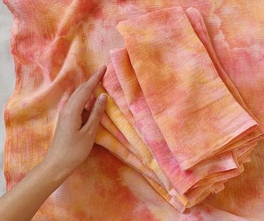 person's hand near dyed cloth napkins