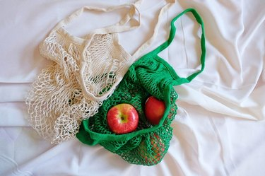 two reusable bags, one with apples