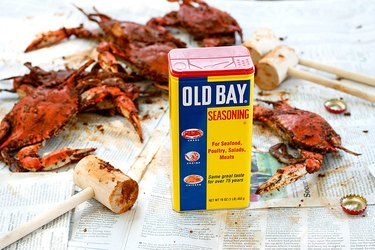 Old Bay seasoning near crab on newspaper